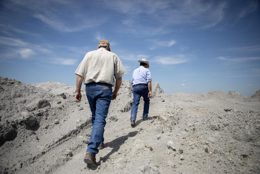 Jason Peeler and his brother TKTK Peeler walk on coal ash from an above ground lignite mine on their family ranch. The mine …