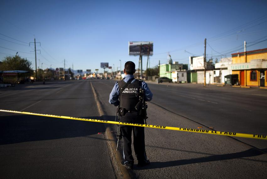 "A municipal police officer at a crime scene in Ciudad Juarez, Mexico. The municipal police force was recently ""purged"" under…"