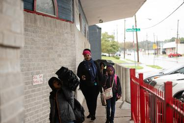 Kimbley Wilson and her three children Knowledge Shallah (front), 6, Sariah Wilson (right), 10, Micah Wilson (back), 9, go into the Braswell Child Development Center in Fair Park after a long bus commute from north Dallas on Oct. 19, 2018.