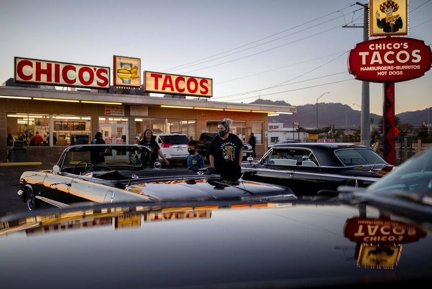 A small group looks at  low rider cars outside of Chico's Tacos, a popular restaurant in El Paso, during a COVID-19 outbreak…