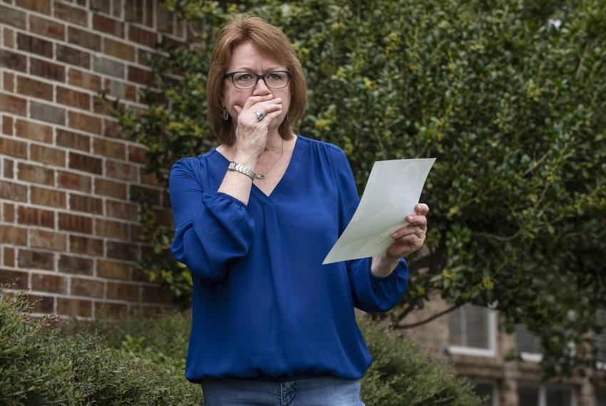 Genny Lutzel covers her mouth as tears fill her eyes while holding a photograph of her mother, Paula Spangler, 80, outside h…