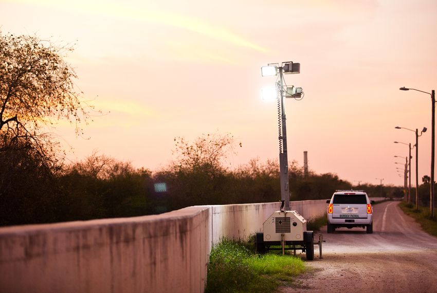 At dusk, Border Patrol agents place mobile floodlights along the levee-fence in Hidalgo County.