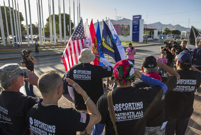 Veterans of the U.S. military who have been deported salute the U.S. flag and flags for the various armed forces on Memori...