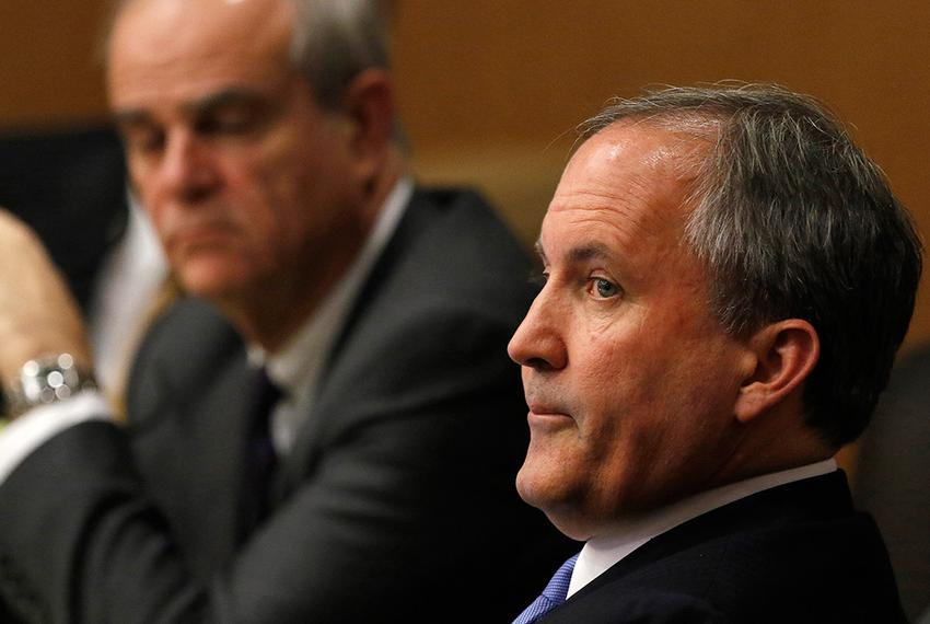 Texas Attorney General Ken Paxton, right, looks at one of the special prosecutors during a pre-trial hearing at the Collin...