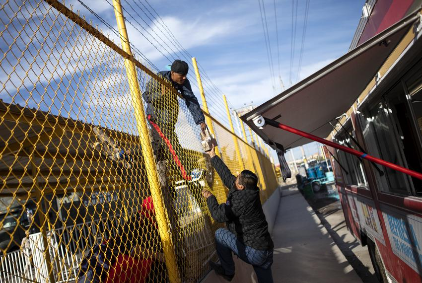 A young migrants reaches for food and coffee from a shelter employee in Piedras Negras. Feb. 18, 2019.
