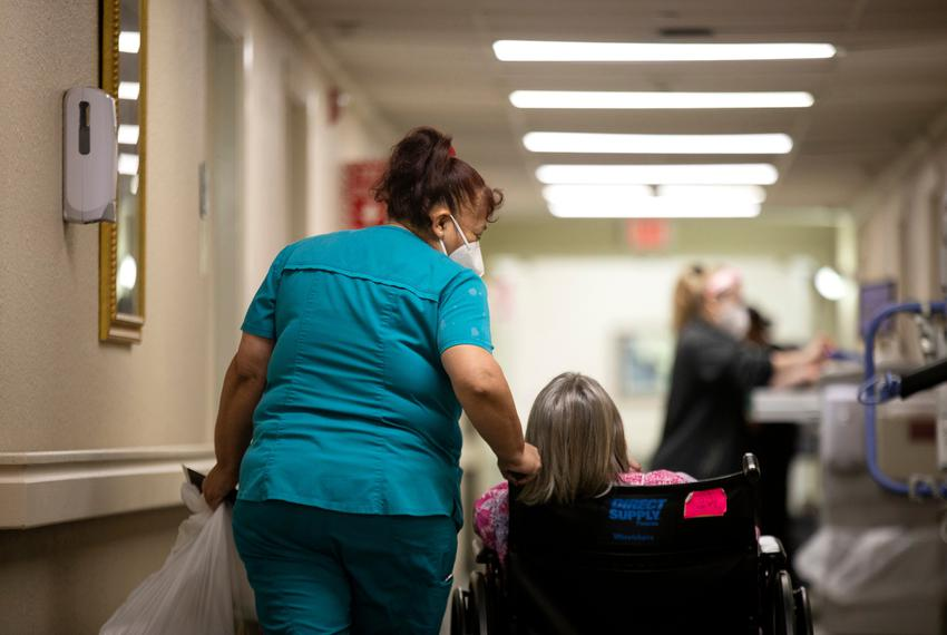 Nursing home employee walks next to a resident in a wheelchair down a hallway.