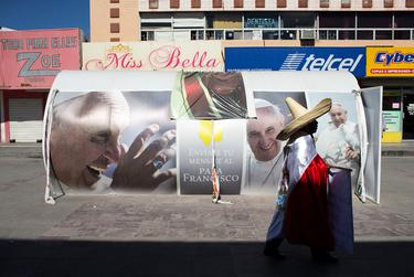 A man in a sombrero and draped with the Mexican flag is seen walking near a Pope Francis display in the center of Ciudad Juárez on Feb. 15, 2016.