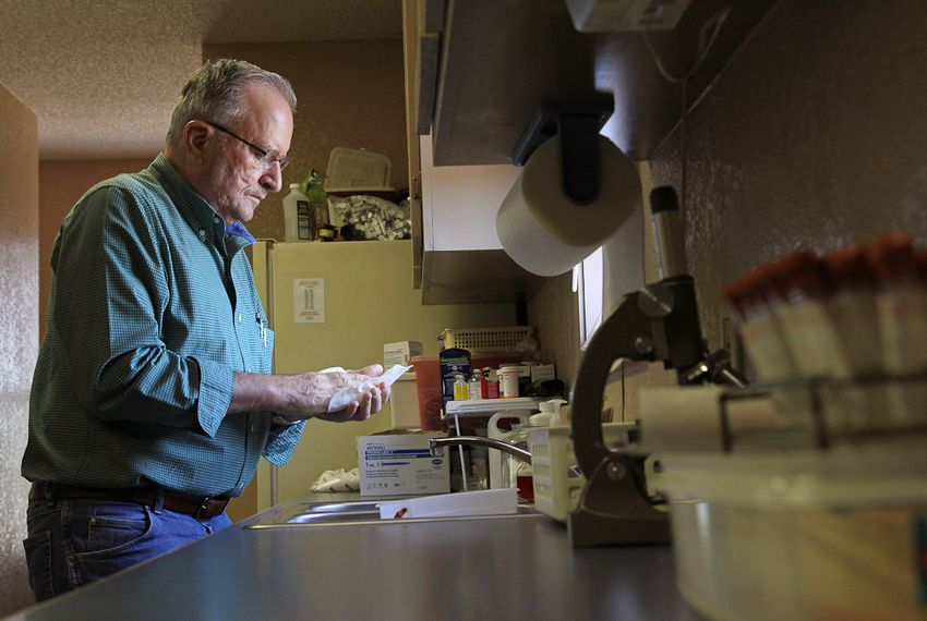 Dr. Roberto Margo cleans his hands after attending to a canine patient. As a result of his large animal work, Margo has had back, shoulder, and arm surgery.