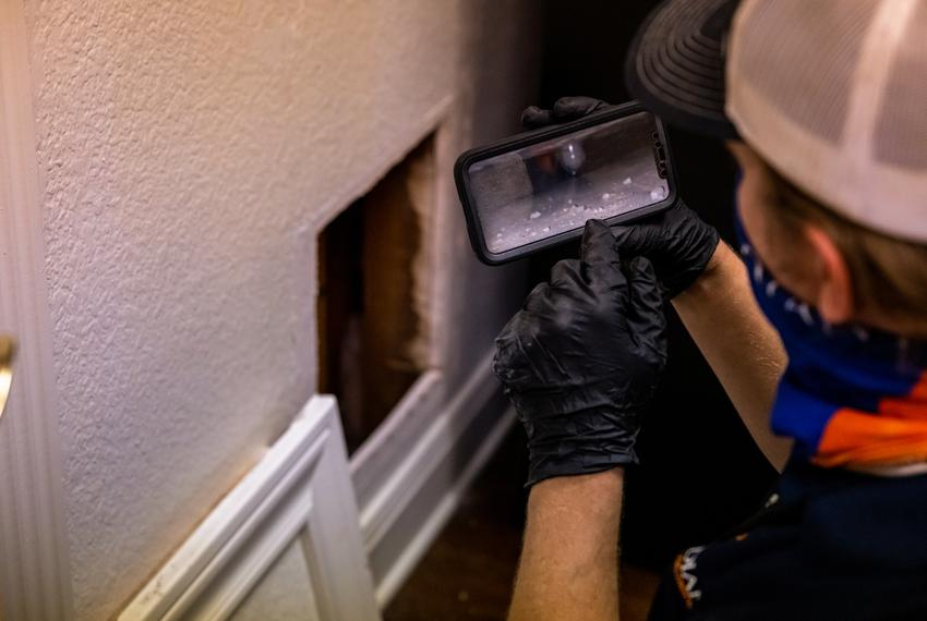 Zachary Shockency, a technician with Radiant Plumbing, uses his phone to take a video of a leaky pipe that caused flooding d…