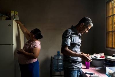 Carlos' parents, Rosa, left and José, right, who live in Olancho, Honduras, take their daily medication for various illnesses such as diabetes, thyroid disease and high blood pressure. Their daughter Lilian, who migrated to Los Angeles, California 14 years ago, has been providing for them ever since.
