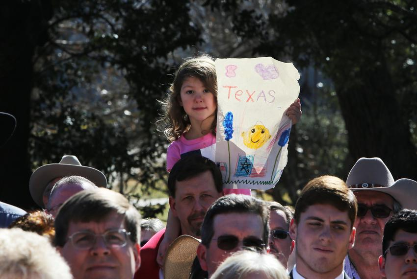At the inaugural celebration, a girl in the crowd holds up a drawing that includes the Texas flag.