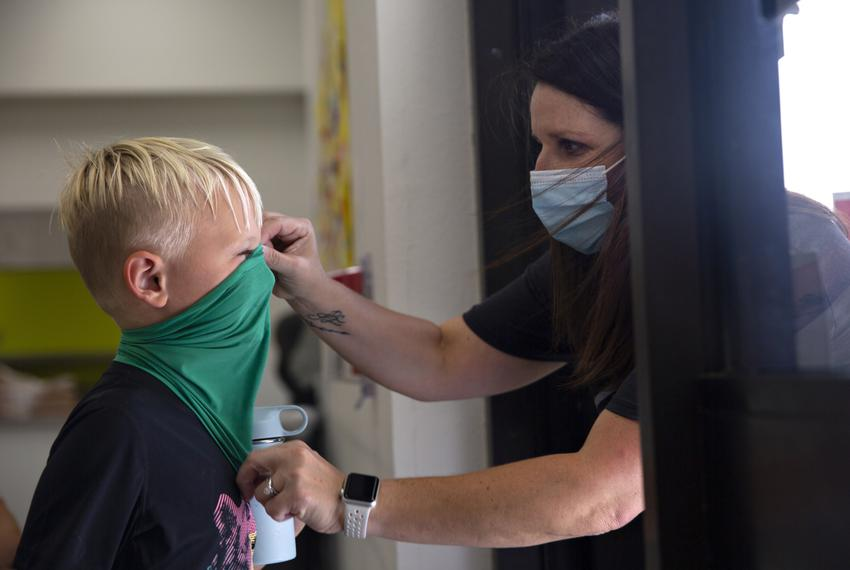 Teachers ensure students have their masks on correctly on the first day of in-person classes at Highland Village Elementary …