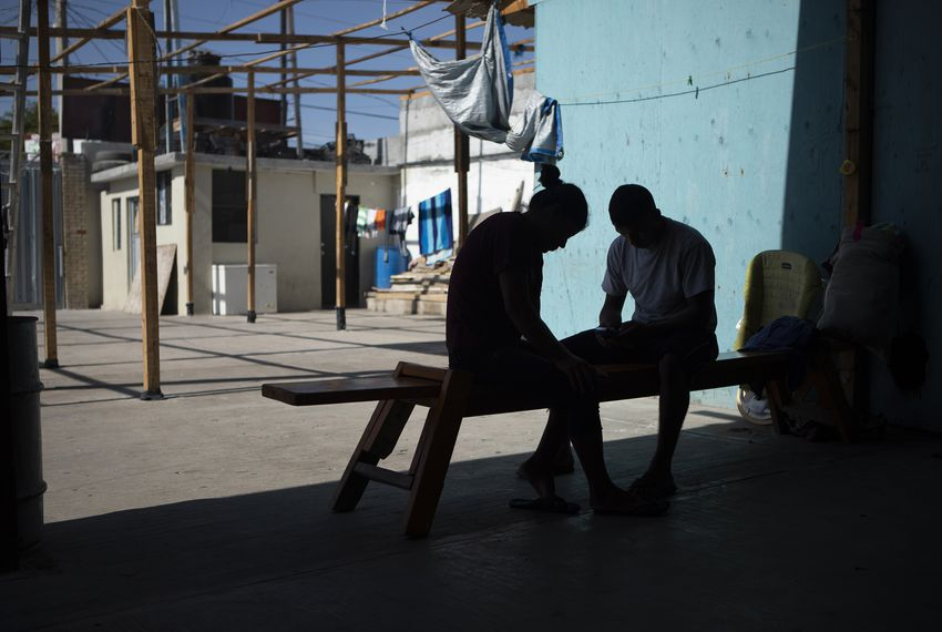 Two migrants sit on a bench at the Casa del Migrante Amar shelter in Nuevo Laredo on July 23, 2019.