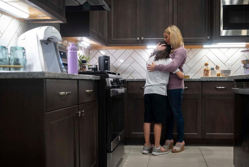 Danielle Miller hugs her child as the family prepares for school in their home in Magnolia on Oct. 21, 2021.