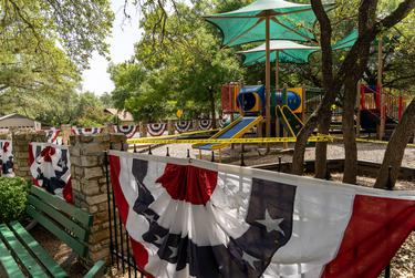 Patriotic bunting lines a closed playground in the Lost Creek neighborhood of West Austin on July 4, 2020.