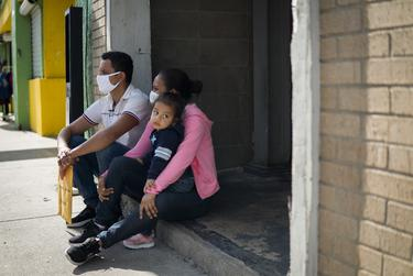 From left: Jose Alfredo Ledezma, 35, and Idxi Martinez, 24, of Honduras, sit with their one year old daughter outside of Catholic Charities Humanitarian Respite Center in McAllen on Aug. 2, 2021.