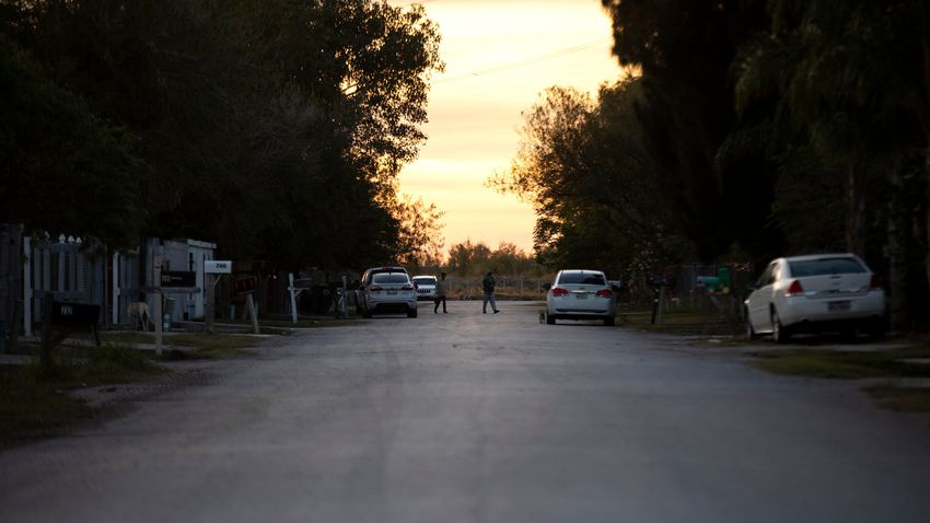 People walk down a road in Donna before nightfall. Dec. 7, 2020.
