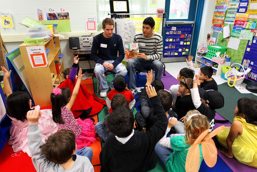 National Honor students Zach Calkins and Aaron Gonzales, seniors at Brandeis High School, read to kindergarten students in a…