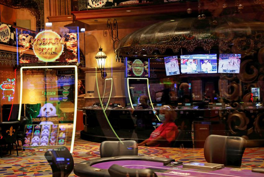 A woman is seen reflected wearing a protective face mask, amid the coronavirus disease outbreak, outside a closed poker room…