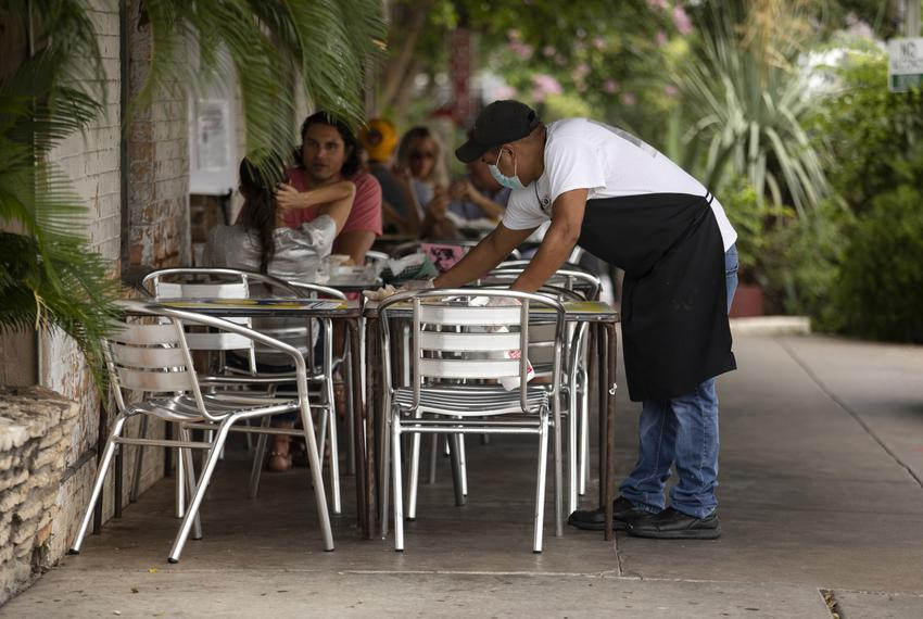 A restaurant worker cleans a table at Güeros Taco Bar in South Austin on June 24, 2020.