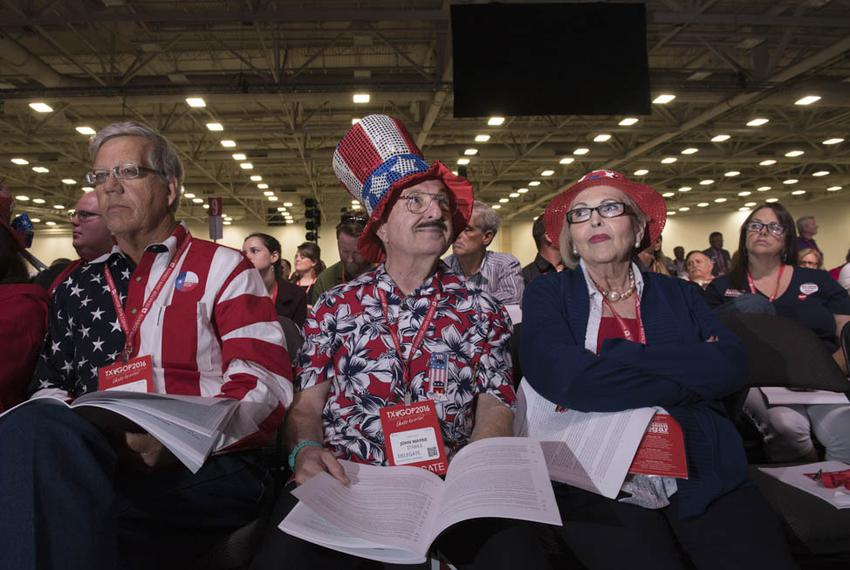 Texas Republicans study the proposed party platform as the debate plays out in Dallas on May 13, 2016.