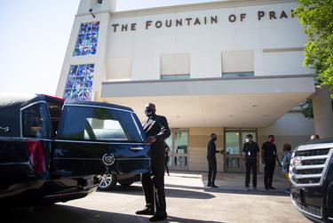 A man closes the back door of a hearse in preparation for the public memorial service honoring George Floyd at the Fountain of Praise Church in Houston on June 8, 2020.