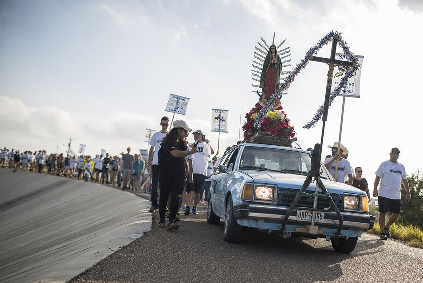 The Save the Mission! Save the River! Resist the Wall! procession atop the levee on the way to La Lomita Mission in Mission, on Aug. 12, 2017.