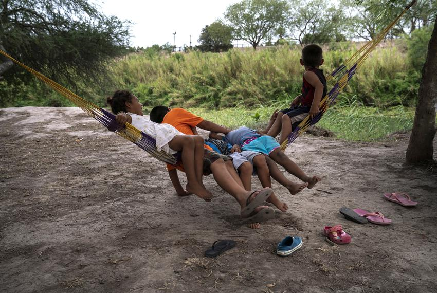 Asylum-seeking children swing in a hammock along the banks of the Rio Grande at a migrant camp in Matamoros, Mexico on May 1…