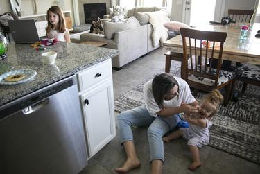 Melissa wipes her youngest daughter's face in the family's home in Katy on Monday, Aug. 24, 2020.