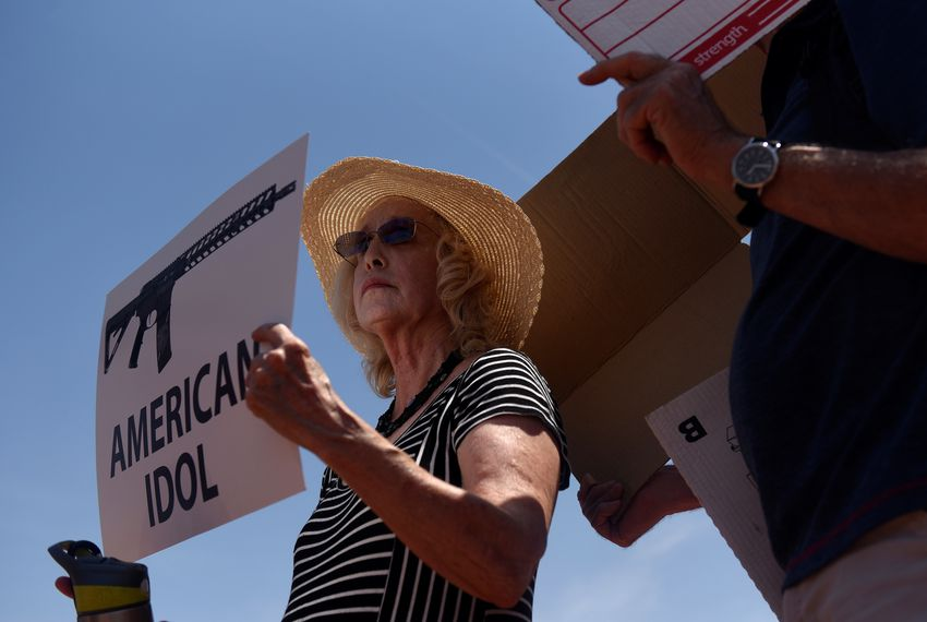Mary Lou Parker protests President Donald Trump's visit four days after a mass shooting at a Walmart store in El Paso.