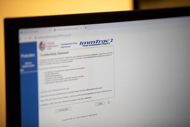Pharmacist-In-Charge Rannon Ching enters information into an online system called ImmTrac at Tarrytown Pharmacy in Austin on Jan. 14, 2021.