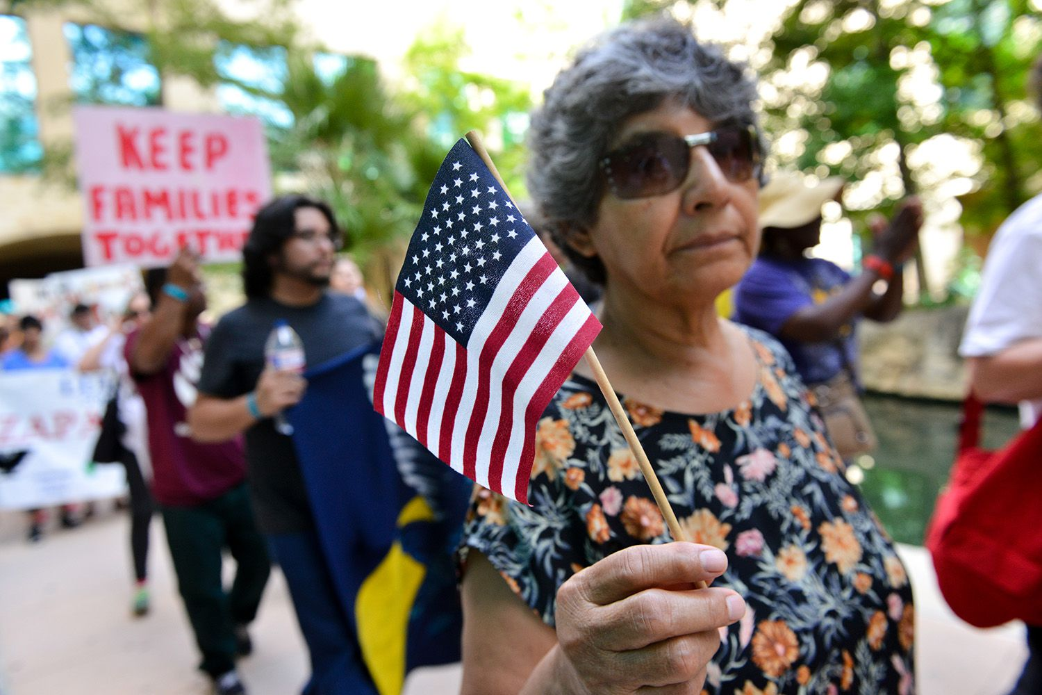 A woman demonstrating against Senate Bill 4, the so-called sanctuary cities law, waves a flag during a march near the San Antonio Riverwalk on June 26, 2017. U.S. District Judge Orlando Garcia is hearing arguments from Texas cities and counties challenging the bill, signed into law by Gov. Greg Abbott.