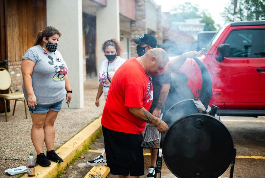 Sam Torres grills chicken wings outside as friends and family of Arturo Valles host a plate lunch fundraiser to aid with m...