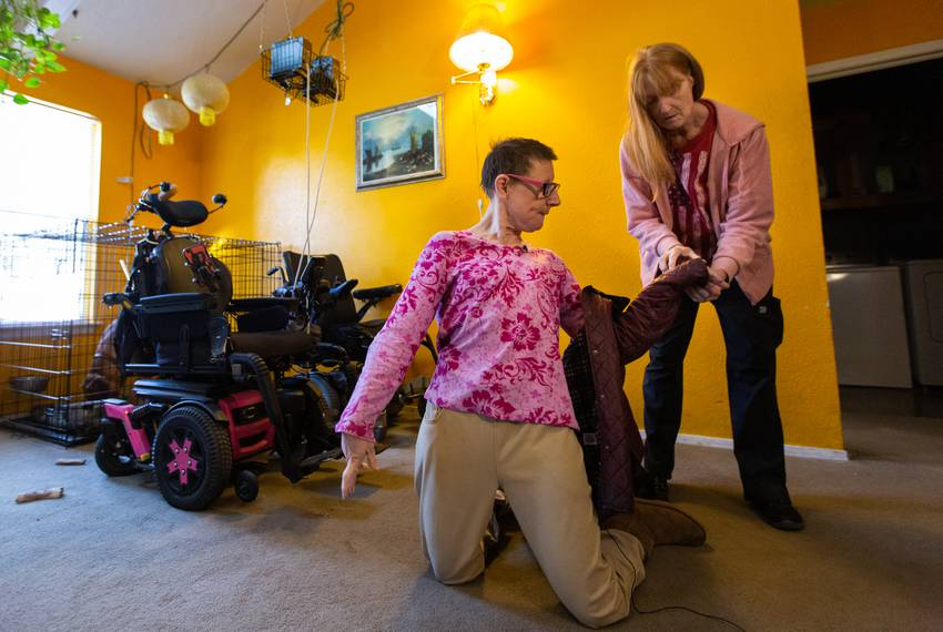 Susie Angel's attendant Sandy White helps her take off her jacket in her home on Jan. 30, 2019.