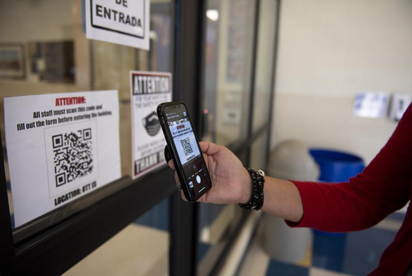 Principal Madeline Bueno demonstrates how staff and visitors are required to scan a code and fill out a form before enteri...
