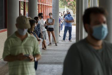 Voters, wearing masks and spread six feet apart, line up outside the Metropolitan Multiservice Center in Houston to vote in the delayed primary runoff election on Tuesday July 14, 2020.