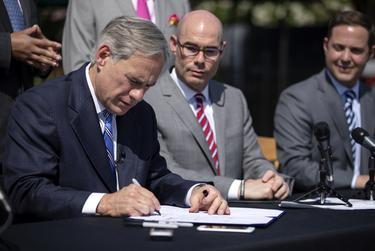 Gov. Greg Abbott signs Senate Bill 2 to limit property tax growth during a press conference at Wally's Burgers in Austin on June 12, 2019.