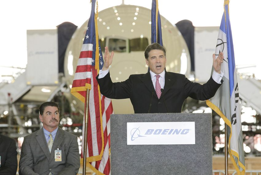 Texas Governor Rick Perry gestures as he speaks at the ceremonial bill signing of HB3727 regarding property tax evaluations of aircraft at the Boeing facility in San Antonio on June 23, 2011.