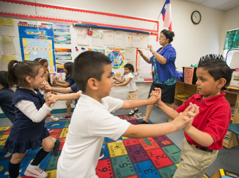 """Pre-K teacher Josefina Pineda teaches her students the concept of """"push"""" by having them join hands and push back and forth in her classroom at the Dallas Independent School District elementary school Cesar Chavez Learning Center in 2013."""