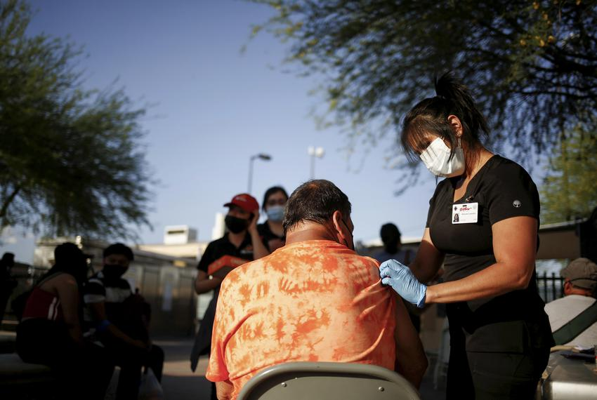 A healthcare worker from the El Paso Fire Department administers the a COVID-19 vaccine at a vaccination center near the San…