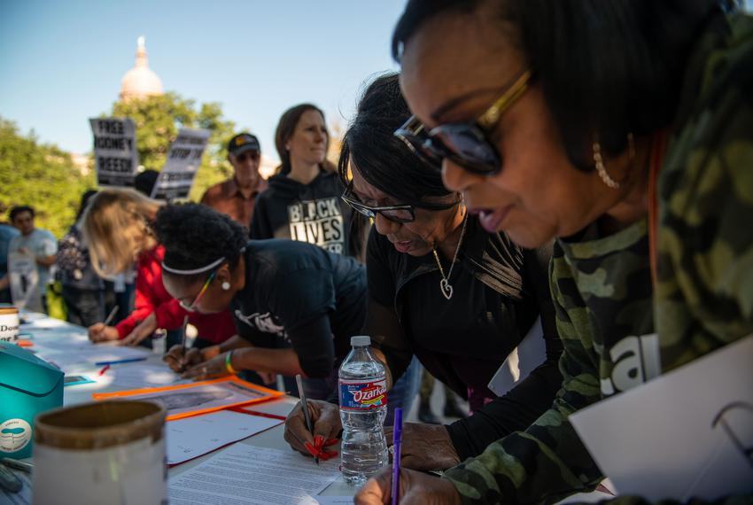 Rodney Reed's cousins Delores Ferguson, center, and Patricia Reed, right sign a clemency letter before a rally in front of t…