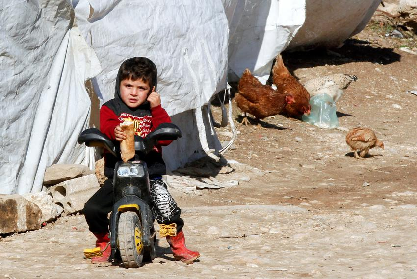 A Syrian refugee boy sits on a bike at a camp in Bar Elias, in the Bekaa Valley, Lebanon on Jan. 13, 2020.