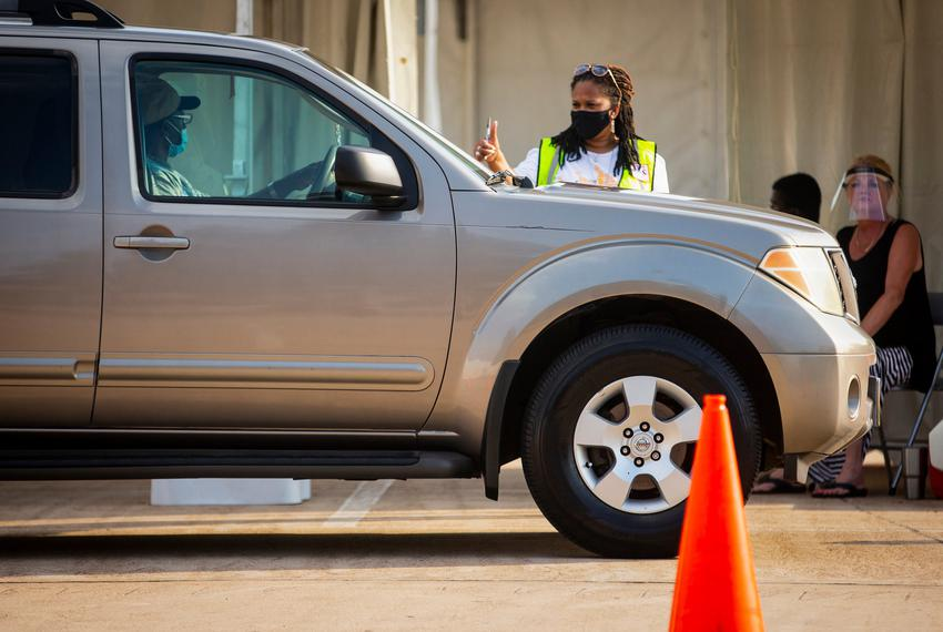 A poll worker gave a thumbs up in one of the drive-through lanes at NRG Stadium in Houston during the first day of early vot…