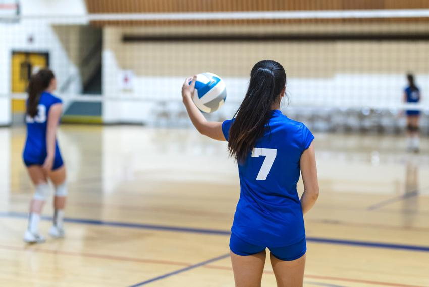 A high school volleyball player gets ready to serve during a game.