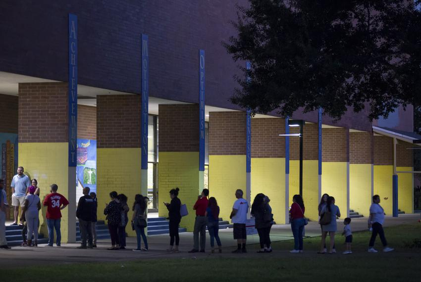 Voter wait in line outside Marshall Middle School,  one of several polling places in Houston being kept open an hour longe...