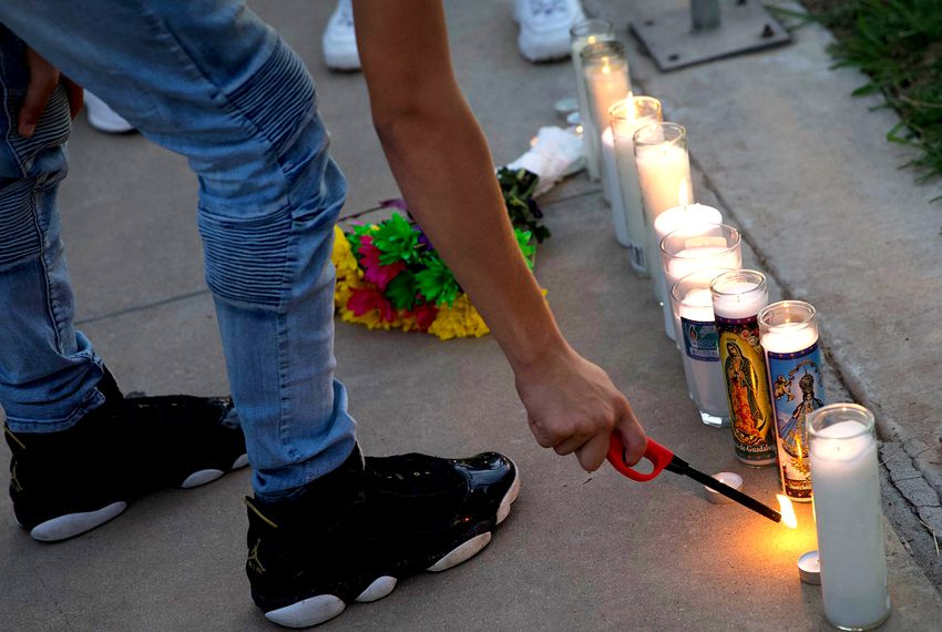 A mourner lights a candle at a vigil for Leilah Hernandez, one of the victims of the shootings in Odessa and Midland.
