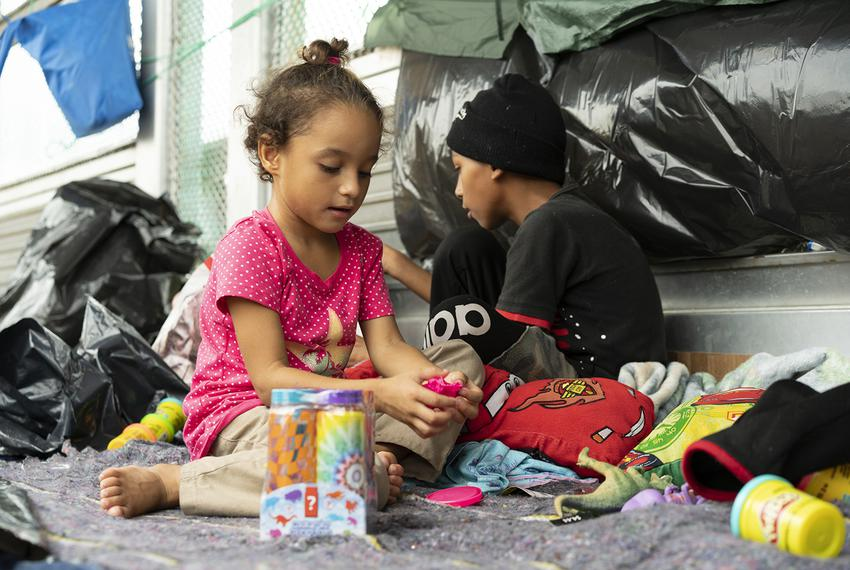 Genesis (left) and Jose Hernandez play with donated toys on the Mexican side of the Brownsville/Gateway Bridge. Their fami...