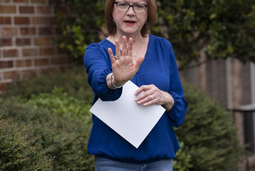 Genny Lutzel stretches her hand as she describes her experience visiting her mother through a window outside of a nursing ho…