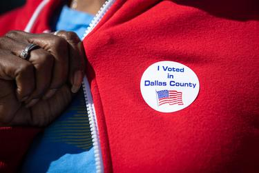 """A woman shows her """"I Voted"""" sticker at Audelia Road Branch Library on the first day of early voting in Dallas on Oct. 13, 2020."""
