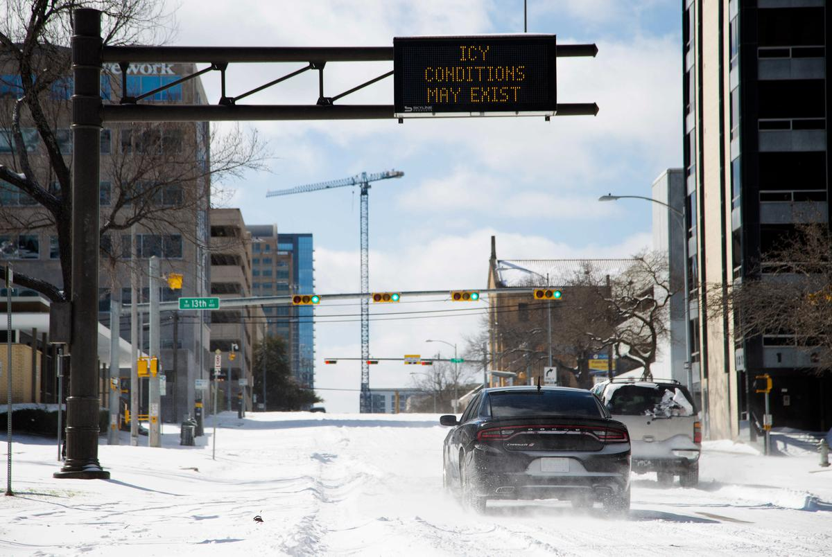 Vehicles attempt to drive uphill through snow and ice on Guadalupe street in Austin, Feb. 15, 2021.